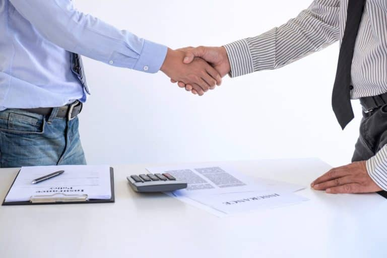 Real estate agent and customers shaking hands together celebrating finished contract after about