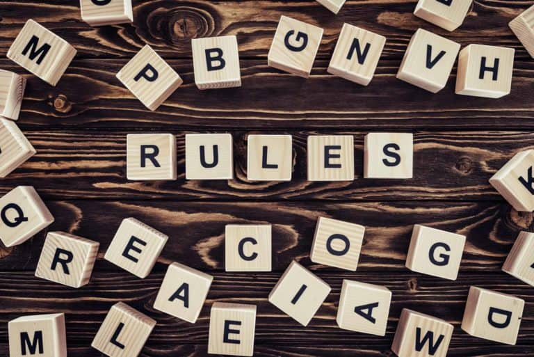 top view of rules word made of wooden blocks on brown surface