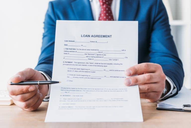 partial view of businessman pointing with pen at loan agreement