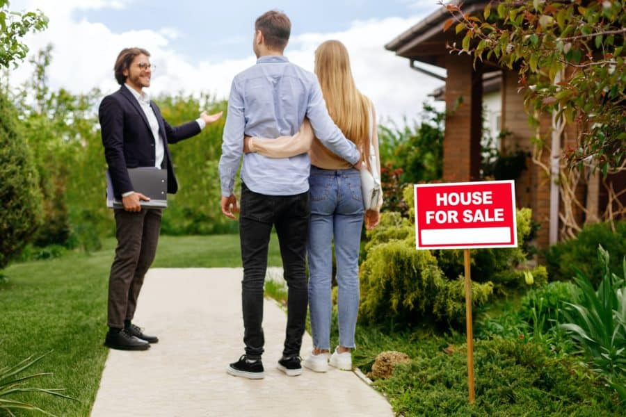 Real estate broker showing house for sale to young couple, outside