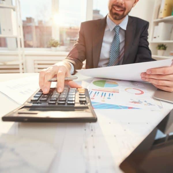 Smiling Businessman Calculating Finances Closeup